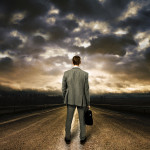 Business man standing in the middle of the road. Dramatic sky above-ratechoice